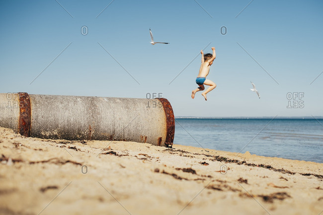 Little boy jumping from a cement pipe into the ocean
