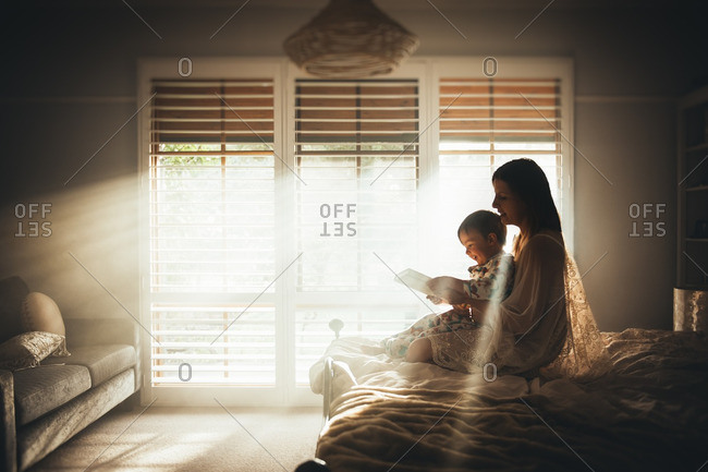 Woman sitting on a bed in a sunny bedroom reading to her son