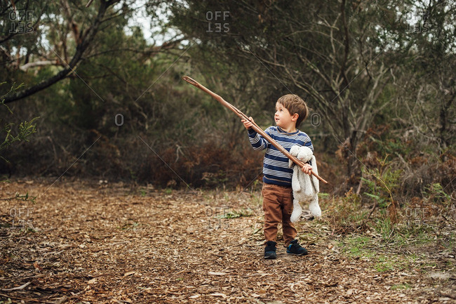 Little boy holding a stick and stuffed bunny in the woods