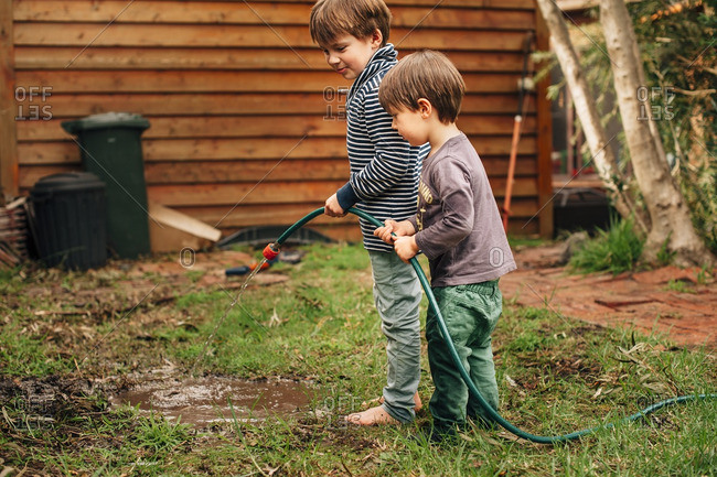 Two brothers making a puddle with a garden hose in the yard