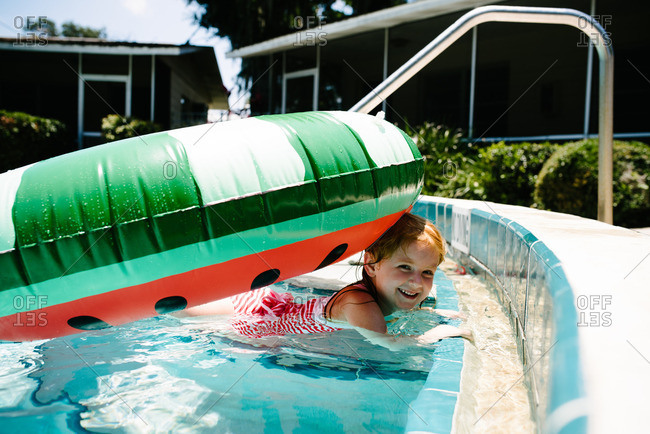 Little girl playing in a pool with a watermelon pool float