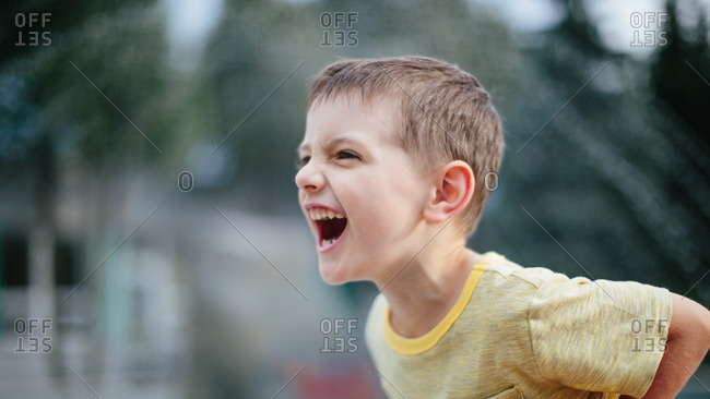 Portrait of a yelling screaming boy showing off his teeth
