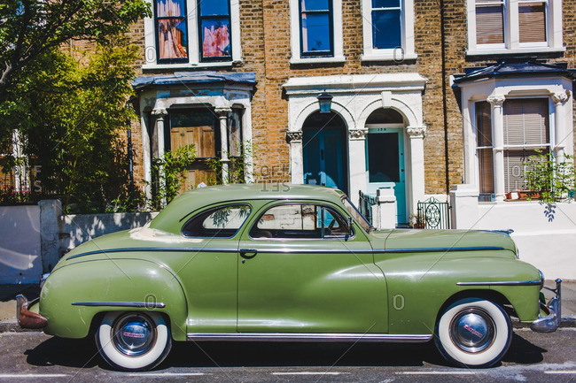 London, England - May 26, 2016: Old car parked outside a group of rowhouses in London