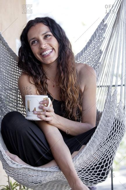 Woman sitting in a hammock drinking coffee