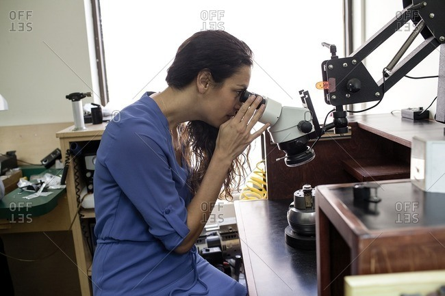 Woman looking through a jewelry microscope
