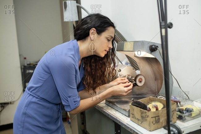 Woman using a buffing wheel in a jewelry studio