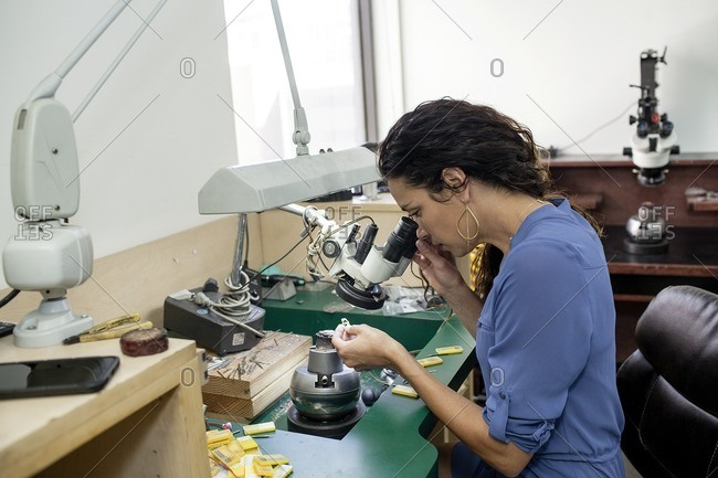 Artist looking through a jewelry microscope