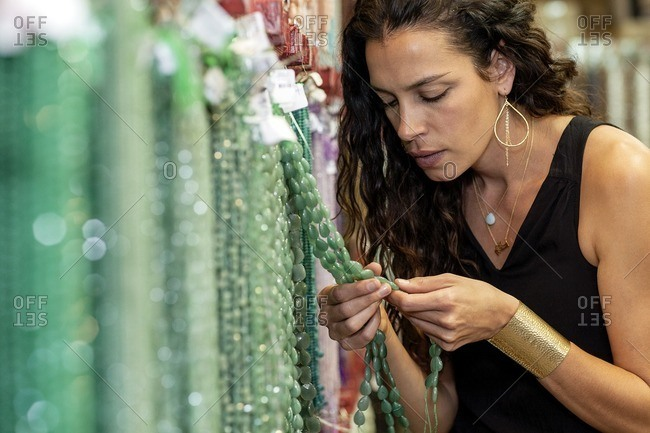 Close-up of a woman browsing through jewelry in a store