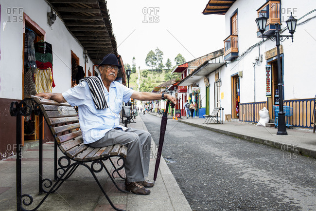 Colombia - February 6, 2014: Man on bench in Colombian town