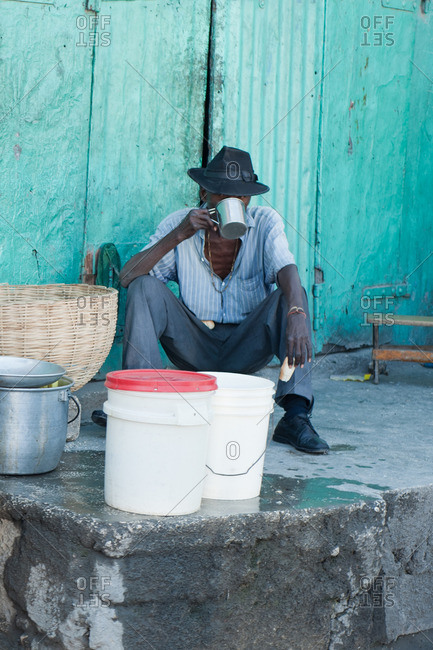 Haiti - February 26, 2011: Haitian man sitting in front of a small ramshackle building