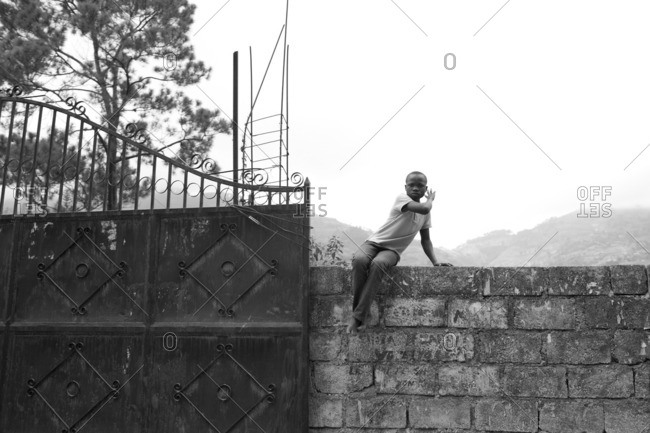 Haiti - February 26, 2011: Haitian man sitting on a wall