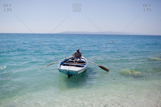 Haiti - February 27, 2011: Haitian man rowing a boat near the shoreline