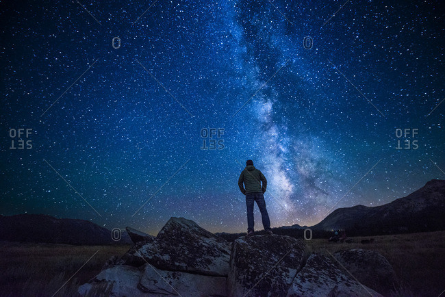 Man standing beneath a starry night sky in Hope Valley near Lake Tahoe, California