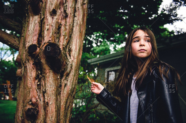Young girl in leather jacket standing next to tree