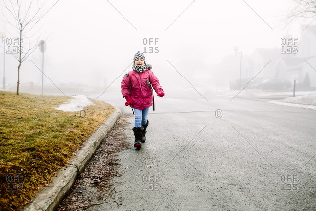 Girl walking down the street on a cold, foggy day in the winter