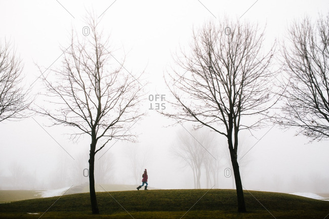 Girl running through a field with her arms outstretched on a cold, foggy day