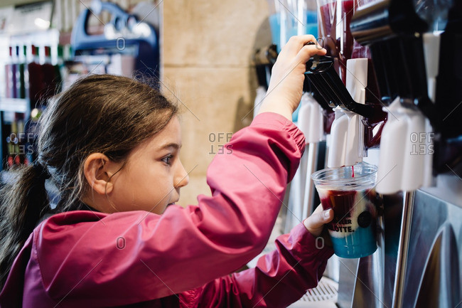 Girl using self-service dispenser to create a sweet drink