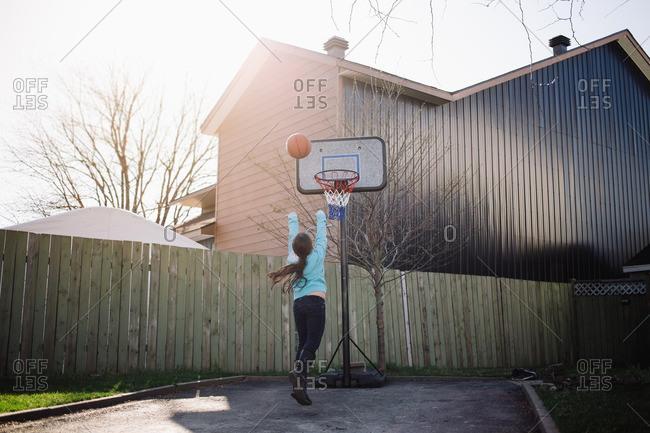 Girl playing basketball in driveway