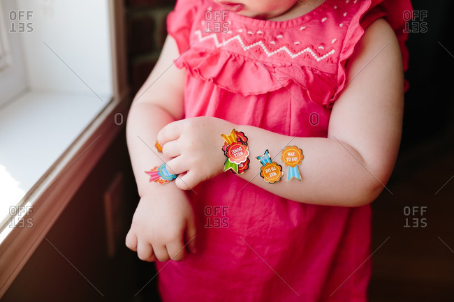 Toddler girl with stickers on her arms