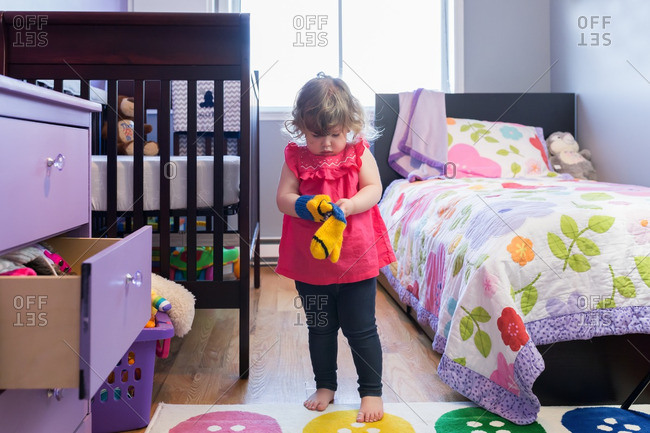 Toddler girl in bedroom putting on pair of mittens