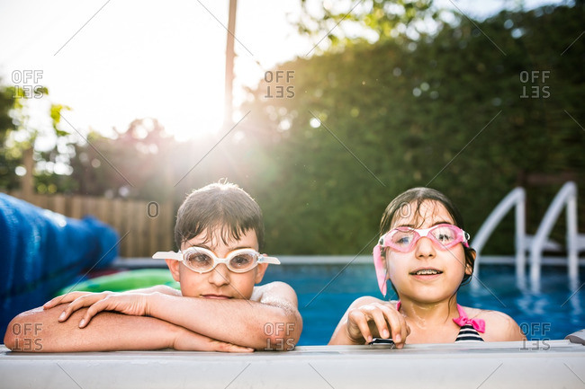 Brother and sister at the edge of a swimming pool