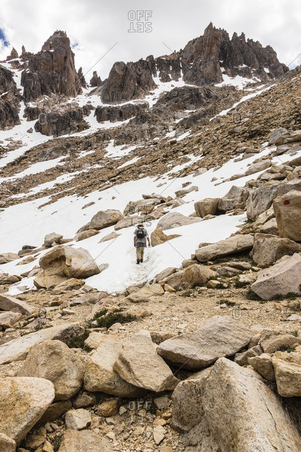 Man hiking in snow in Patagonian valley in spring, Argentina