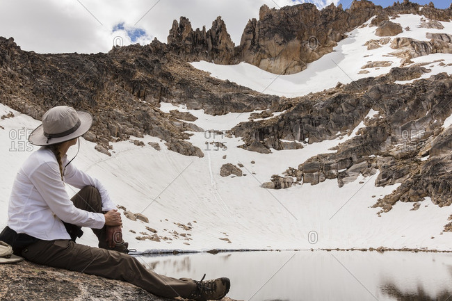 Hiker resting on shore of Schmoll Lagoon in Cerro Catedral, Argentina