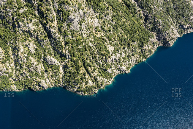 Aerial view of cliffs meeting blue water
