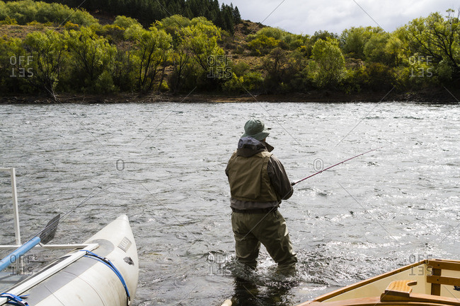 Back view of fly fisherman in river, Argentina