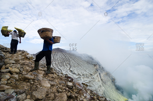 East Java, Indonesia - May 27, 2016: Men with baskets in mountains
