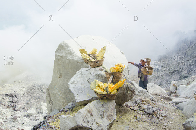 East Java, Indonesia - May 27, 2016: Man by goods in mountains