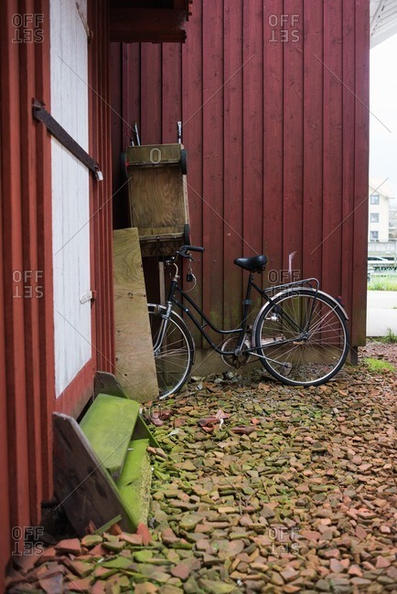 Bicycle parked against the side of a building