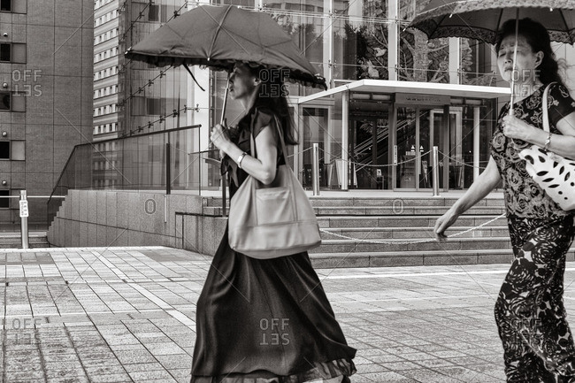 Tokyo, Japan - August 9, 2015: Women with umbrellas walking