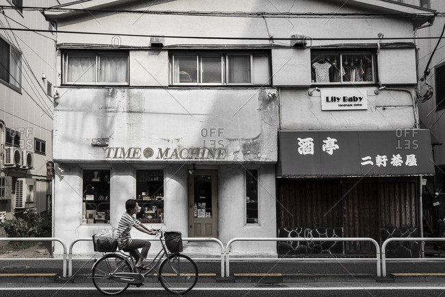 Tokyo, Japan - August 7, 2015: Woman cycling past old storefront in Shimokitazawa