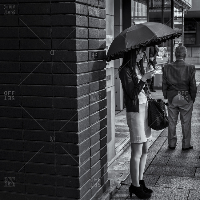 Tokyo, Japan - October 12, 2015: Woman with umbrella checking phone