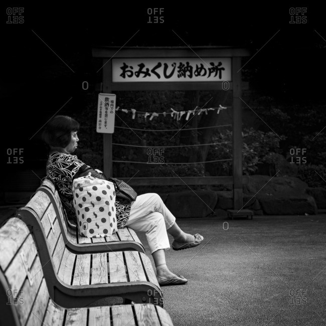Tokyo, Japan - August 21, 2015: Woman resting on bench in Sugamo