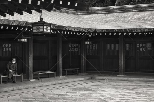 Tokyo, Japan - March 21, 2015: Man on bench at Meiji Shrine