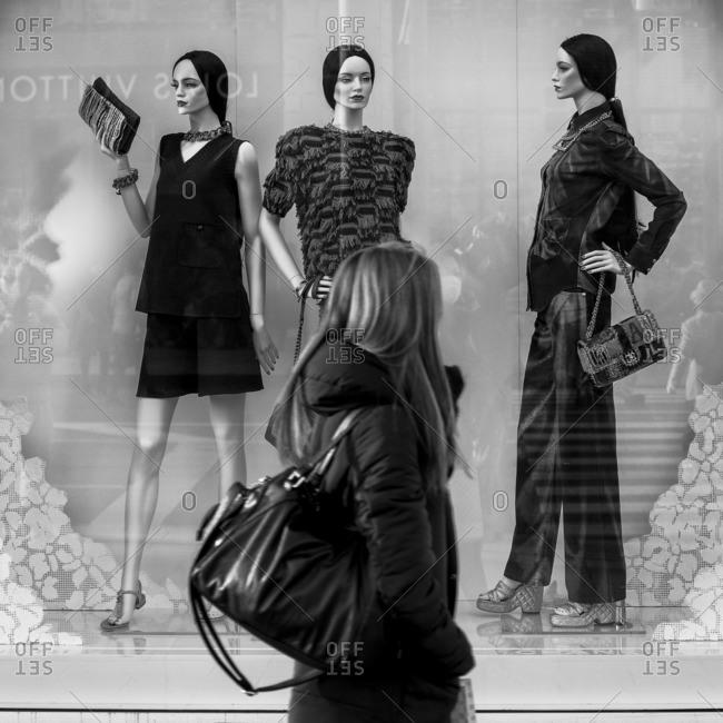 Tokyo, Japan - February 1, 2015: Woman walking by store display