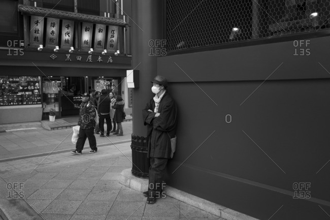 Tokyo, Japan - December 6, 2015: Man leaning on temple gate
