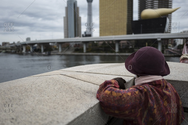 Elderly lady looking across Sumida River in Tokyo