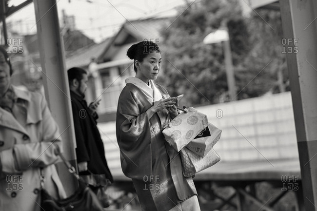 Tokyo, Japan - March 13, 2016: Woman in kimono at train station