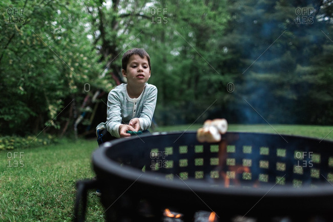 Little boy toasting marshmallows in a backyard fire pit