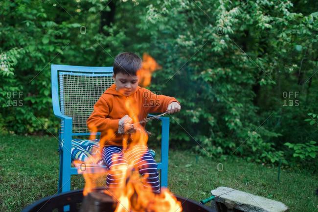 Boy sitting by a bonfire