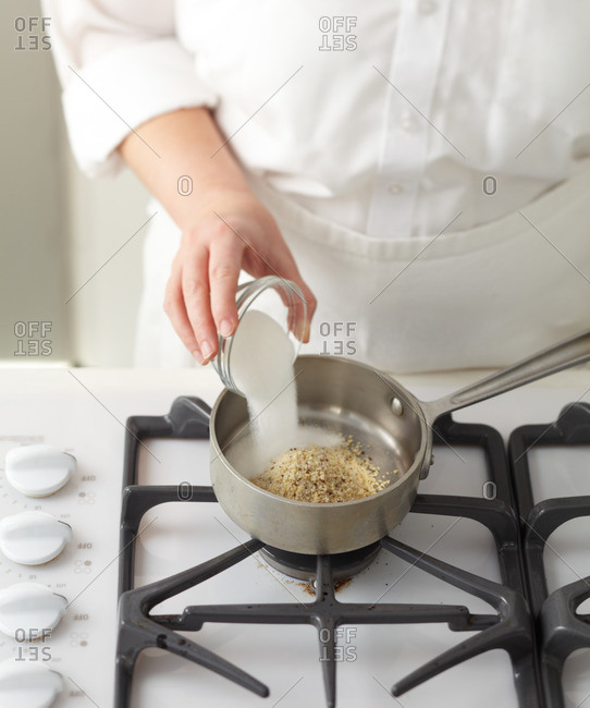Baker pouring sugar into a saucepan on the stovetop