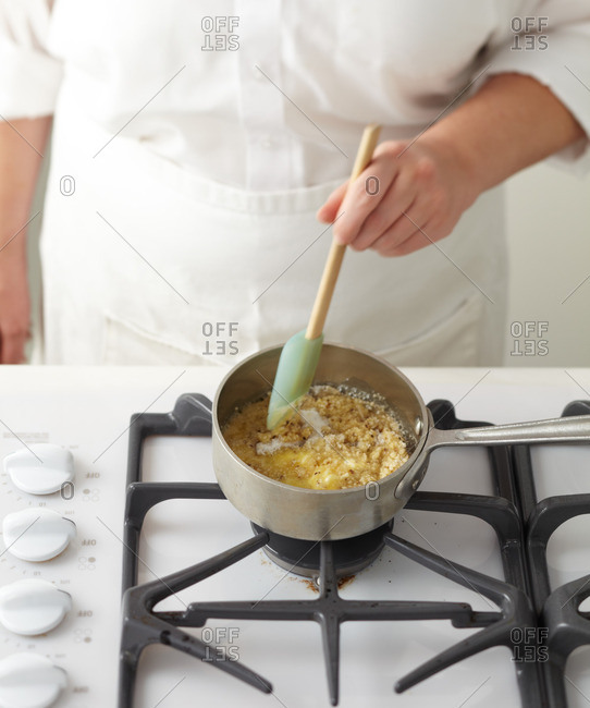 Cook stirring cookie ingredients in a saucepan on the stovetop