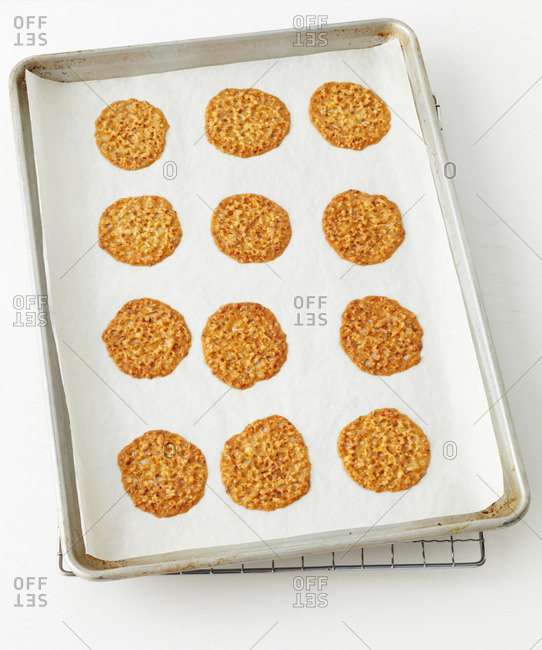 Freshly baked almond lace cookies on a baking sheet