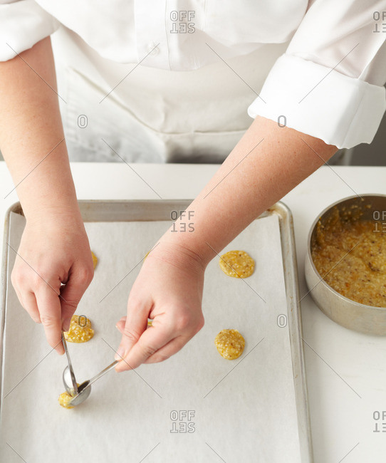 Baker dropping spoonful of dough onto baking sheet to make almond lace cookies