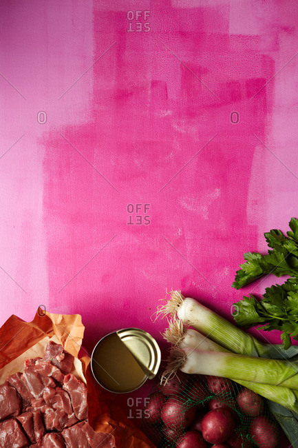 Ingredients for a beef stew arranged on a painted pink background