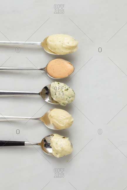 Row of spoons with various savory butter