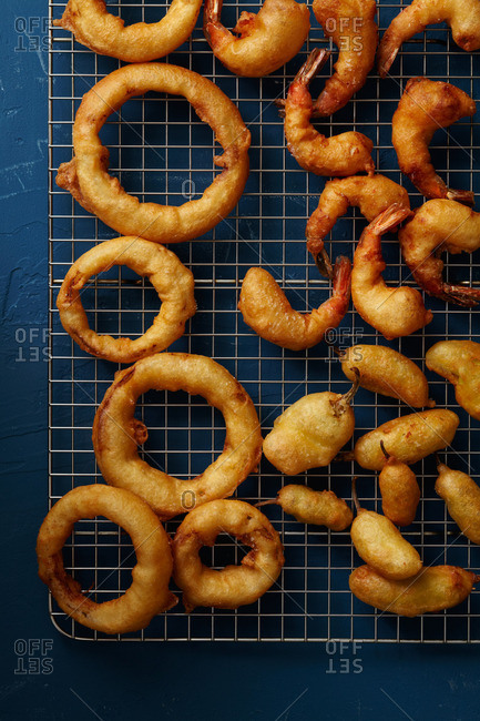Overhead view of a wire rack covered with onion rings, fried shrimp, and jalapeno poppers